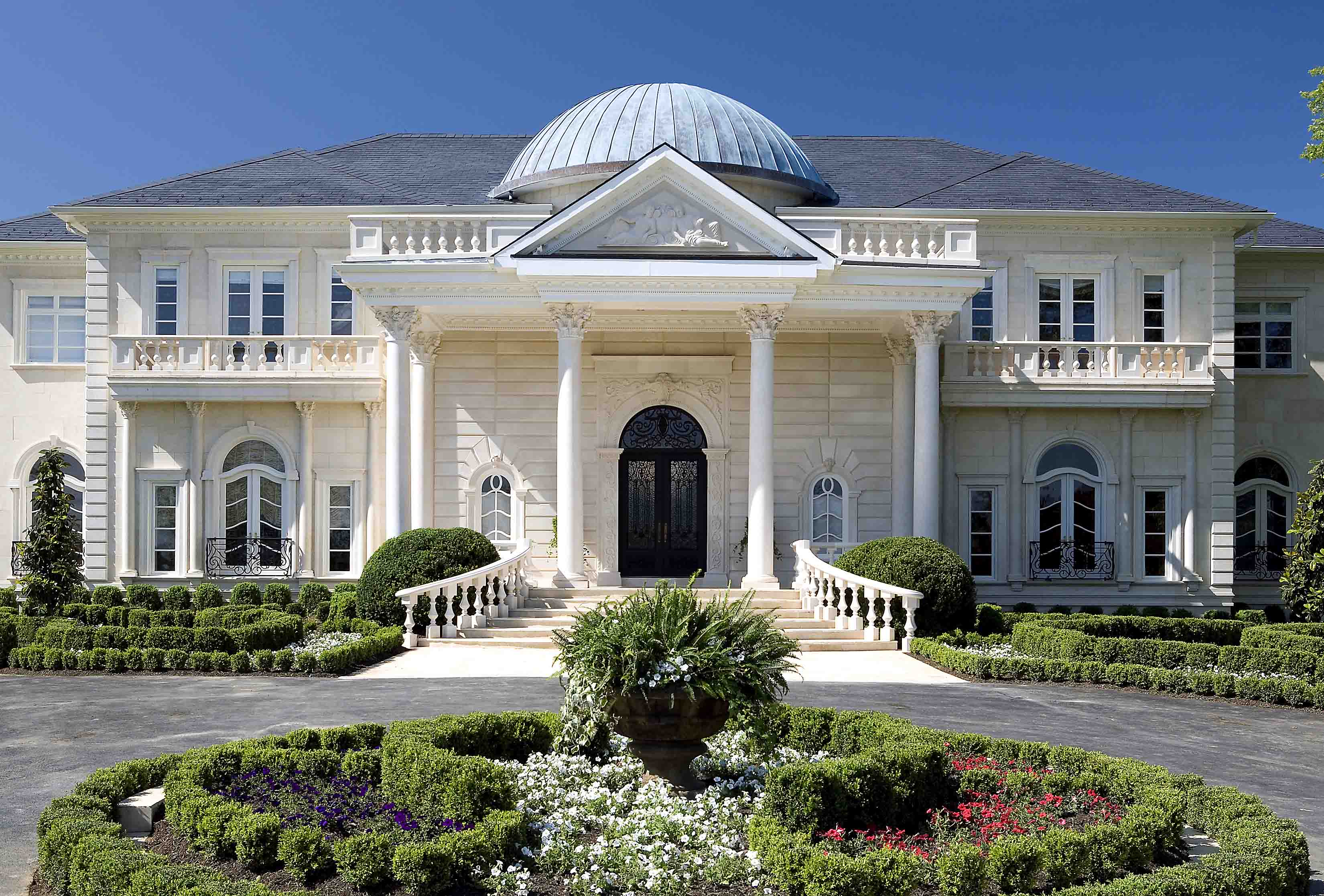 Entrance of a mansion with dome and white columns with a circular driveway and fountain