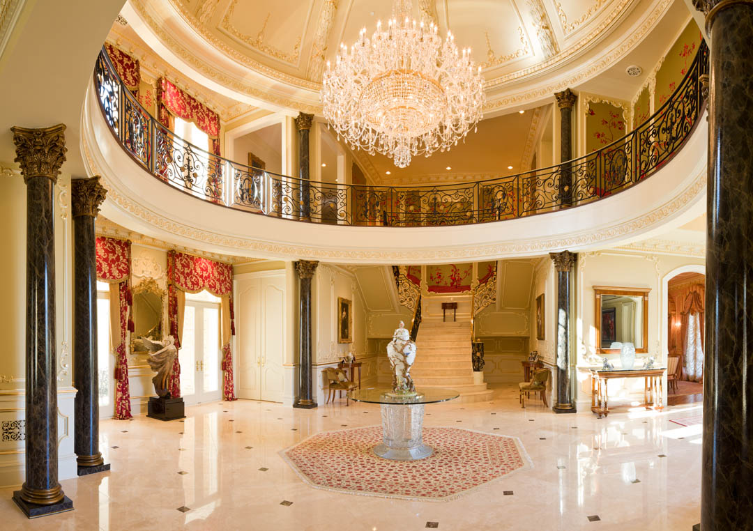 Luxury foyer in mansion with Lalique table, crystal chandelier, marble columns and red accents
