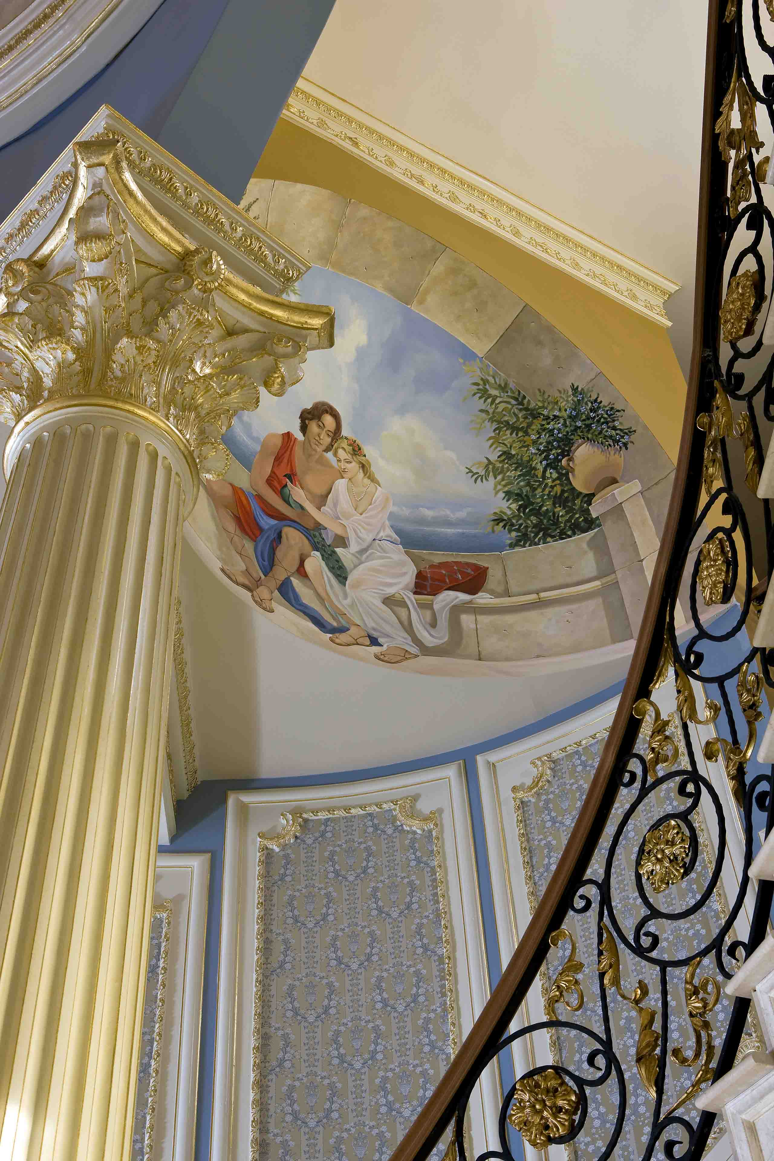 Mural painted in dome of mansion with gold and beige columns and blue and gold walls