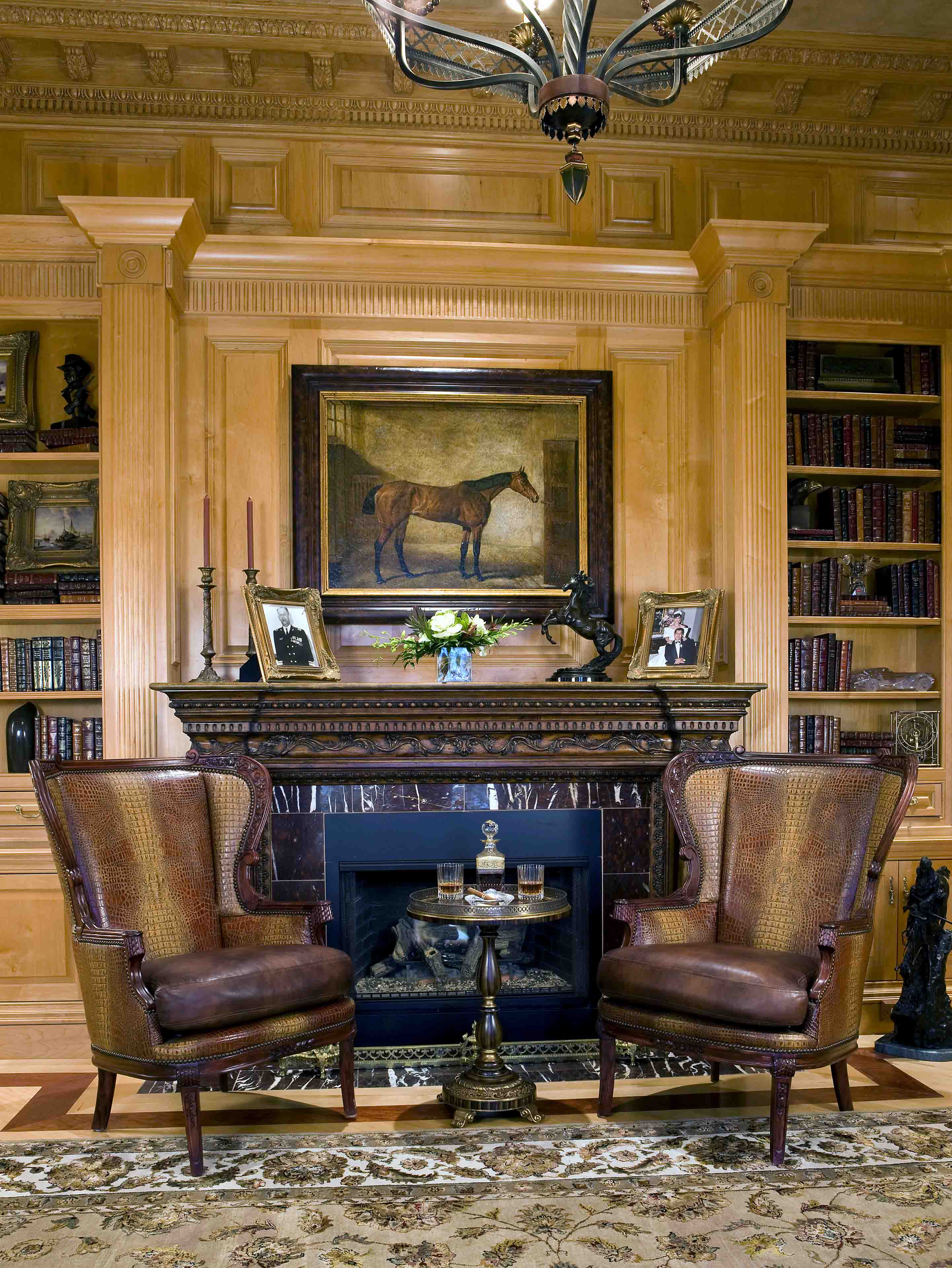 Custom cabinetry with fireplace and two leather seats in home office in mansion in Potomac, Maryland