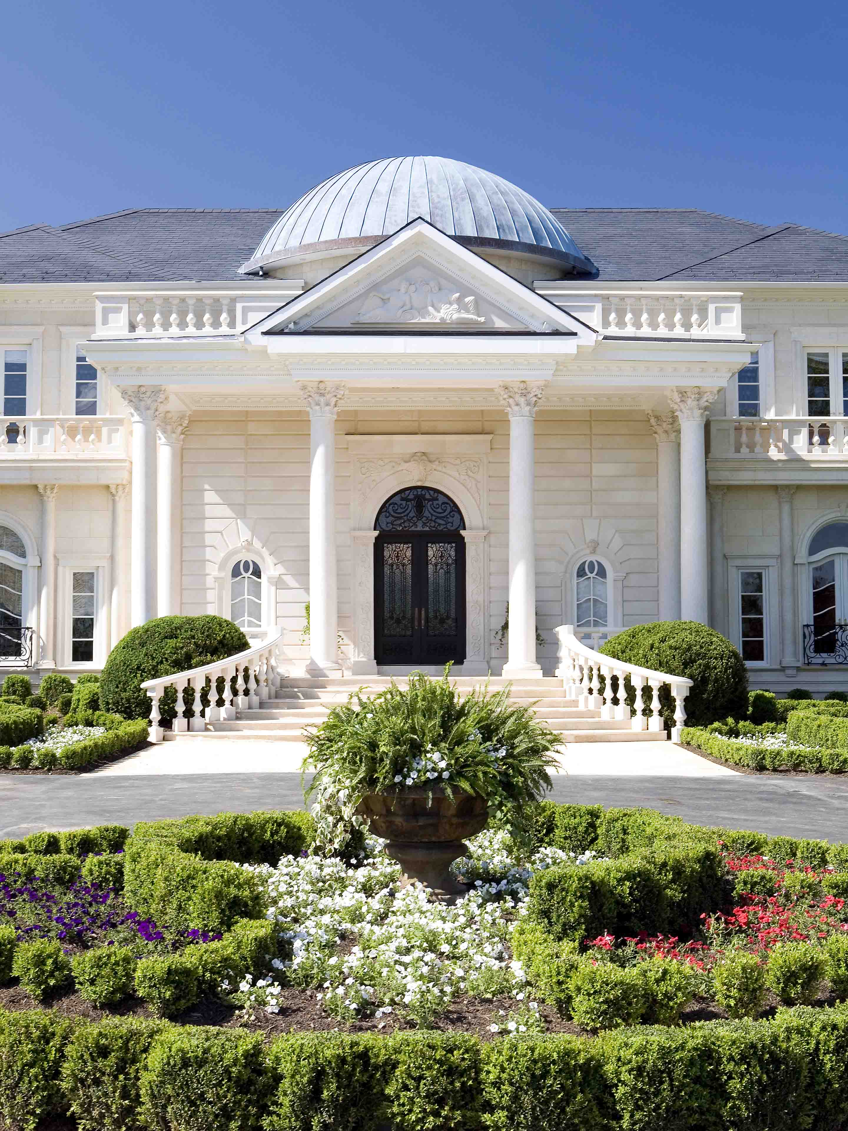 Entrance of mansion with a dome and columns with circular driveway