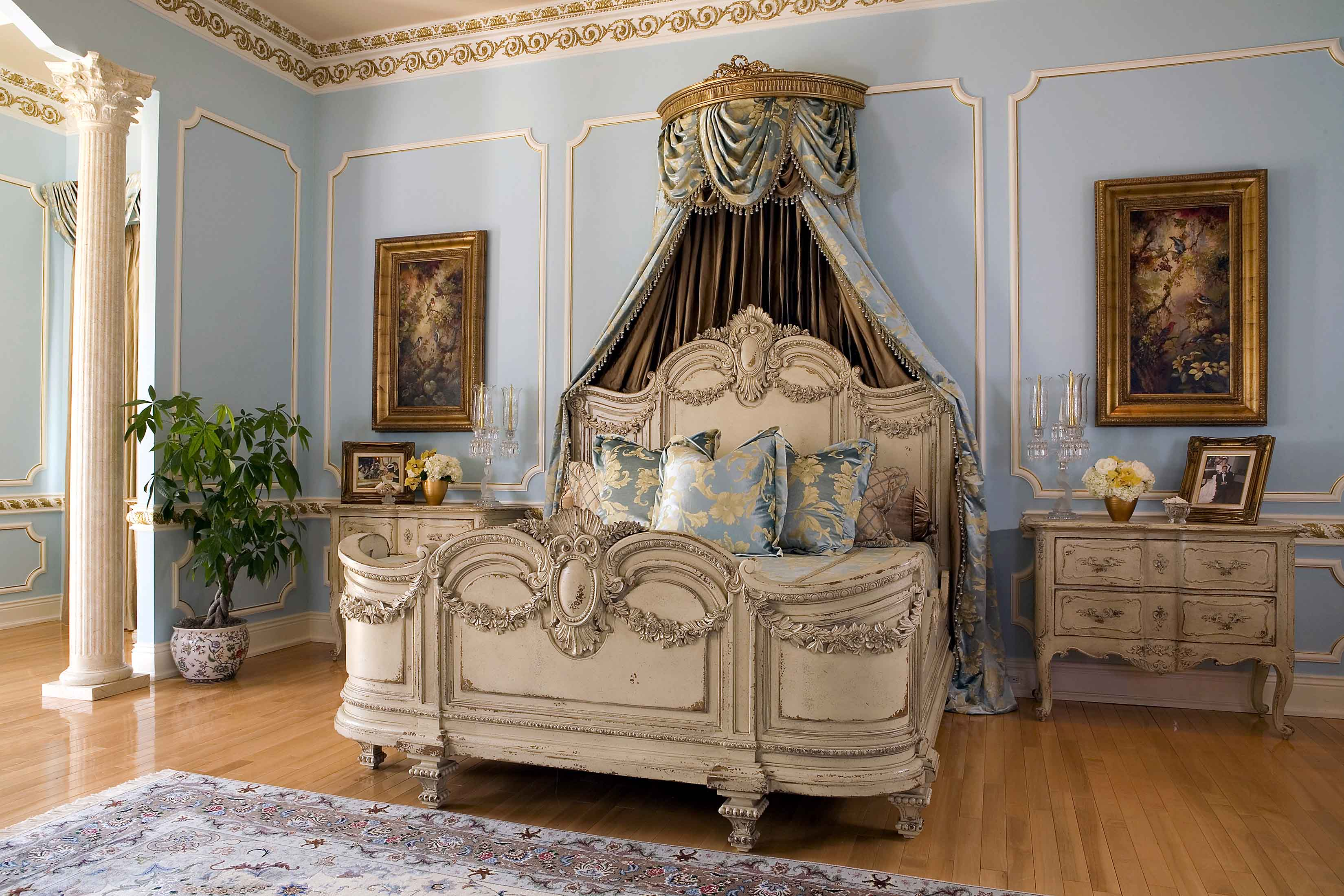 Master bedroom with blue walls, gold crown molding and antique bedroom furniture