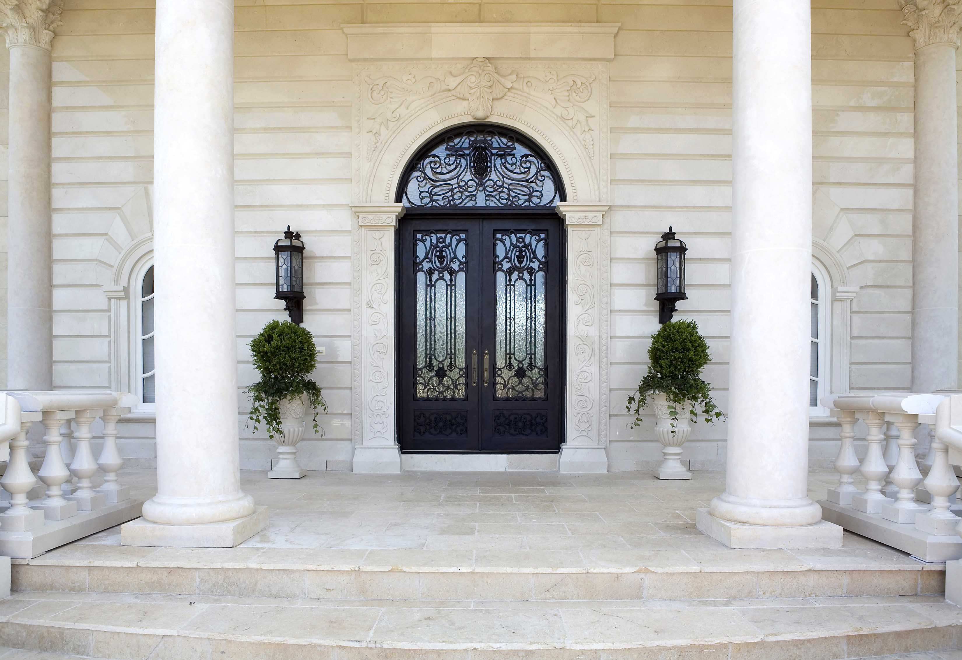 Entrance of mansion with double doors made of steel and glass with white columns