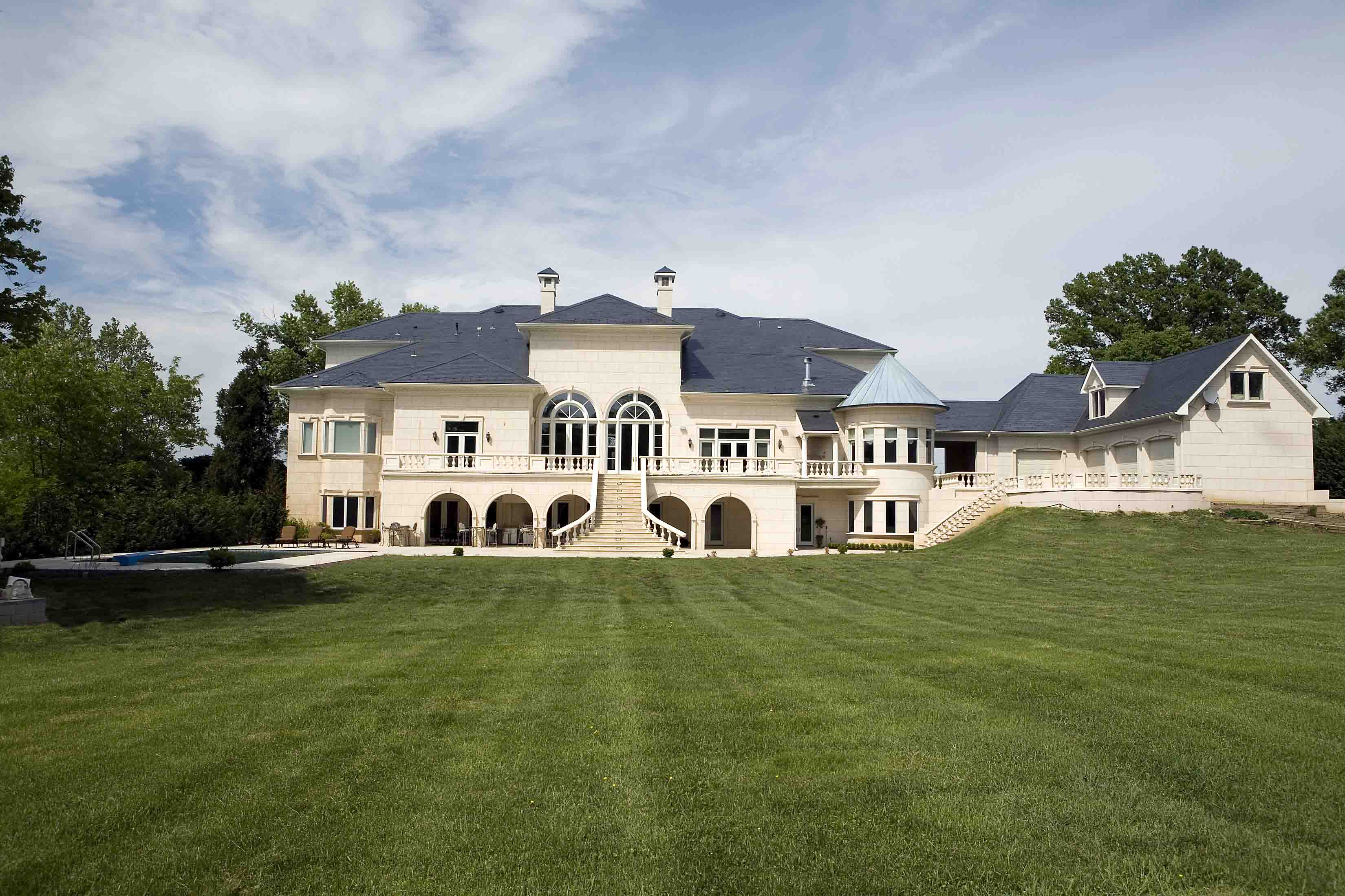 Backyard of mansion with pool with staircase of mansion in Potomac, Maryland