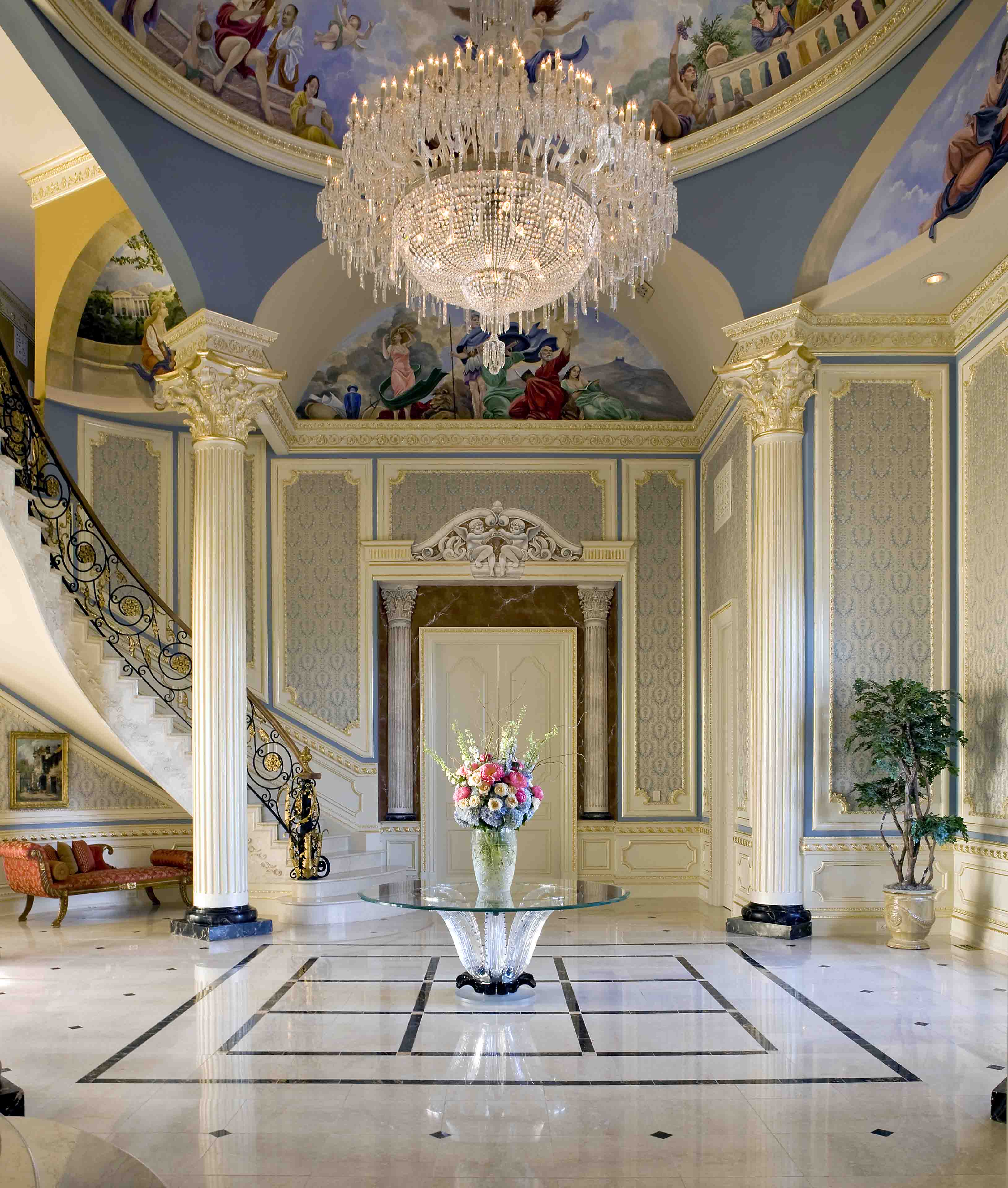 Custom foyer with murals, a Lalique circular table with custom wall panels and crystal chandelier