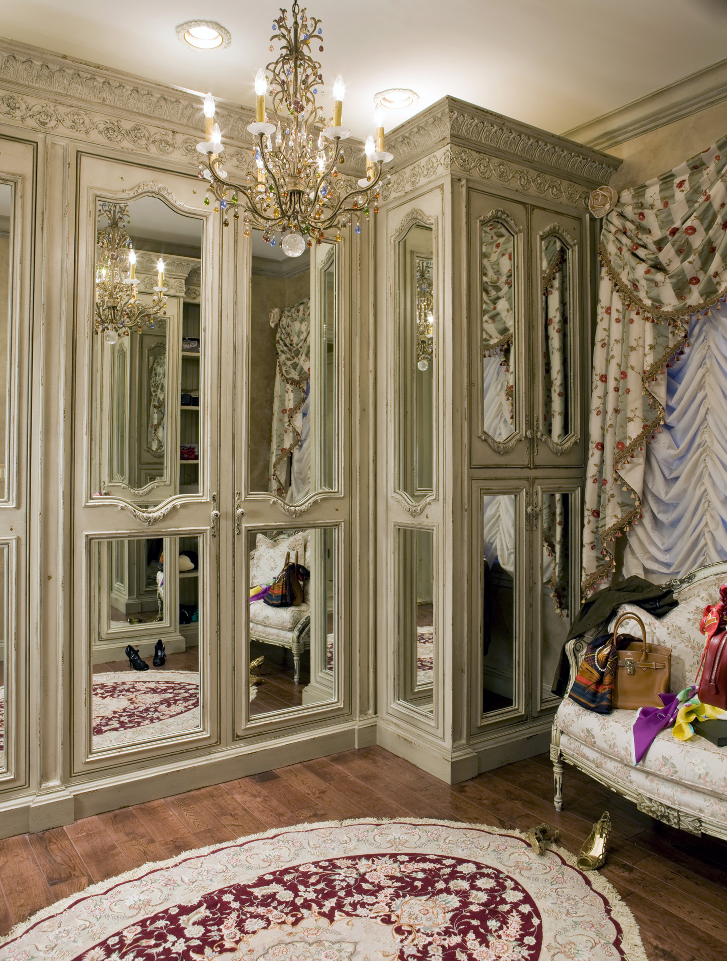 Master closet with antique cabinetry with seating area